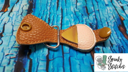 Guitar pic key fob in the hoop embroidery file by spunky stitches.